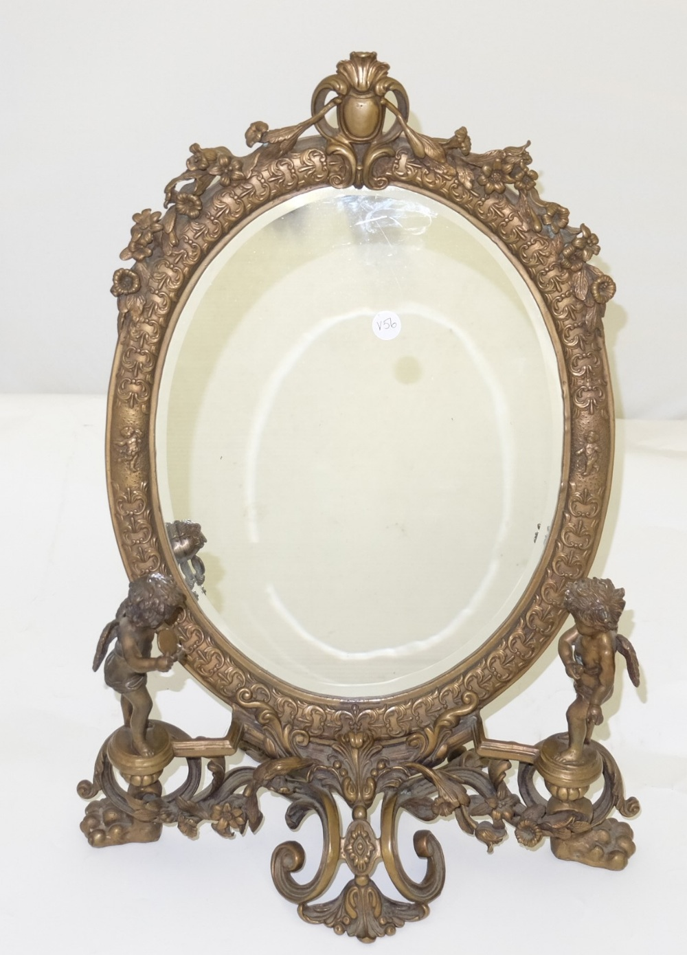 Lot 36 - Mid 20th C decorative brass table mirror, oval shaped and bevelled with floral mounts, the base