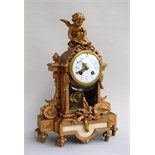 An antique French gilt bronze mantel clock, surmounted by a winged cherub, with two doves to base,