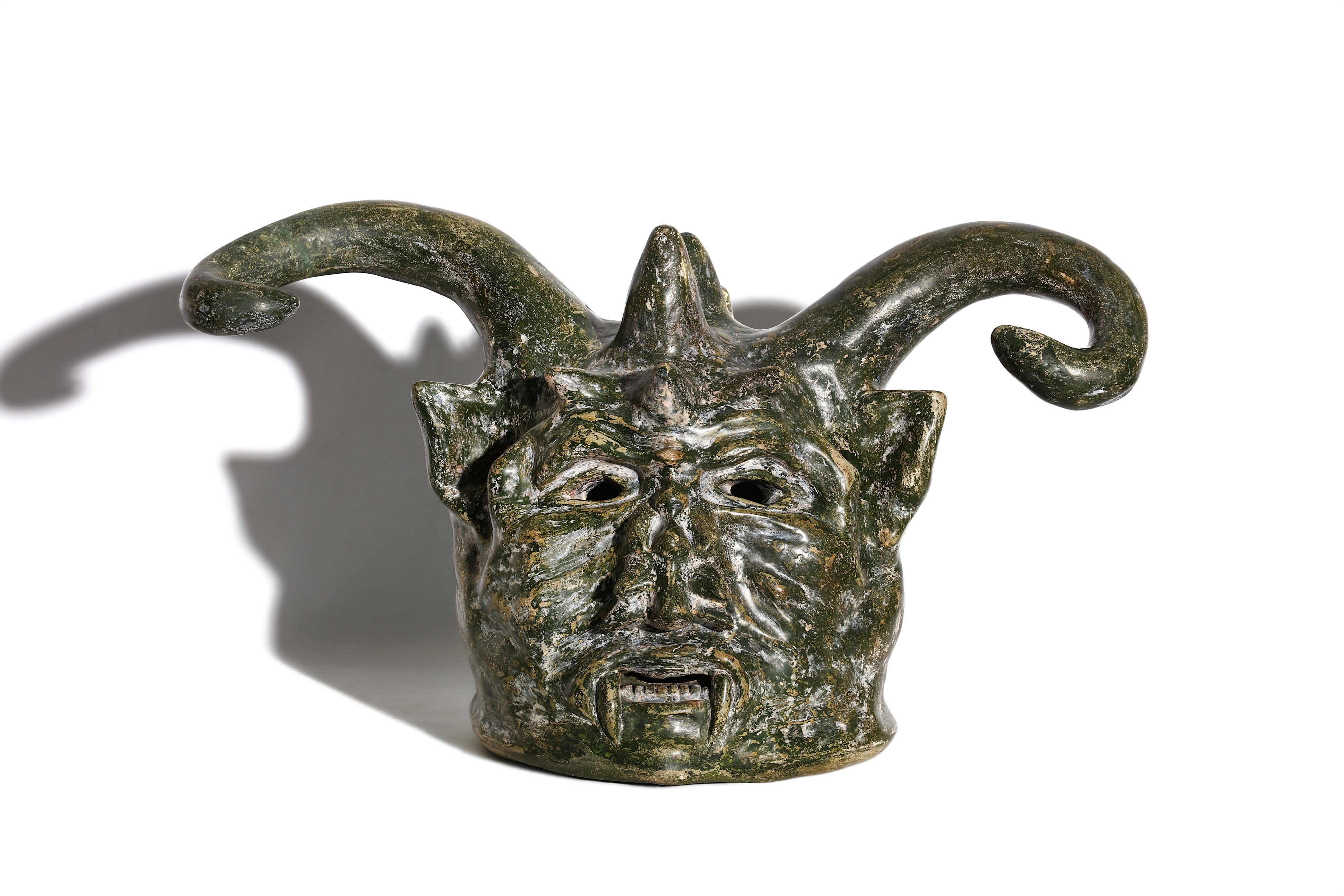 Lot 57 - A MYSTERIOUS AND LARGE 19TH CENTURY PAINTED TERRACOTTA HEAD OF A DEVIL, DATED 1873