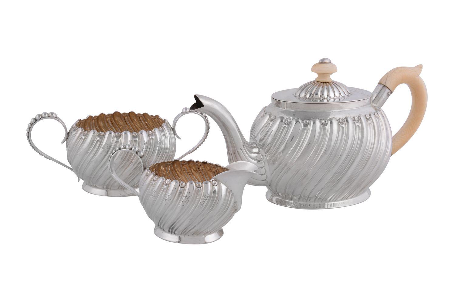 ϒ A Victorian silver and ivory oval three piece bachelor's tea service by Hilliard & Thomason