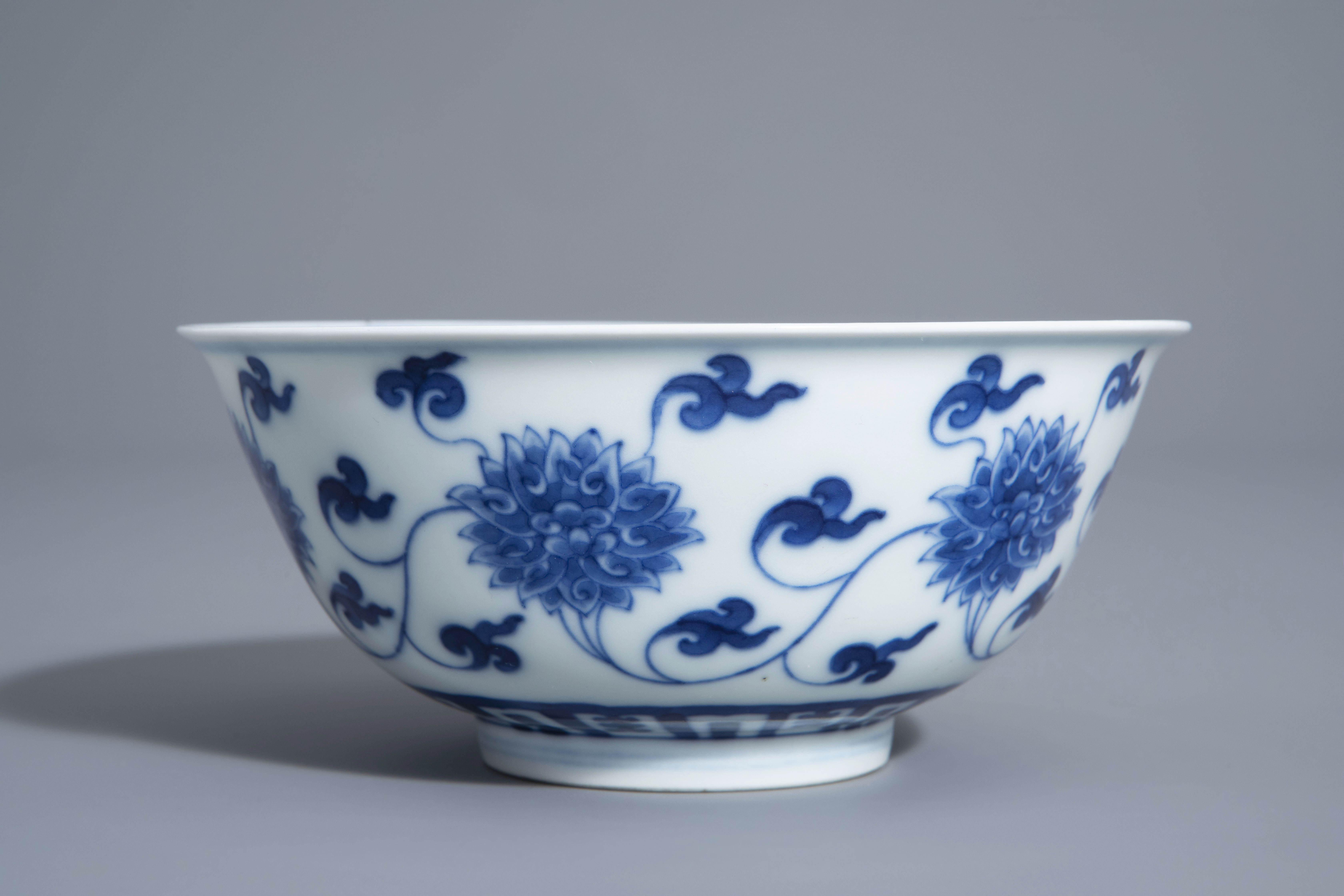A Chinese blue and white 'lotus scroll' bowl, Kangxi mark, 19th/20th C. - Image 5 of 8