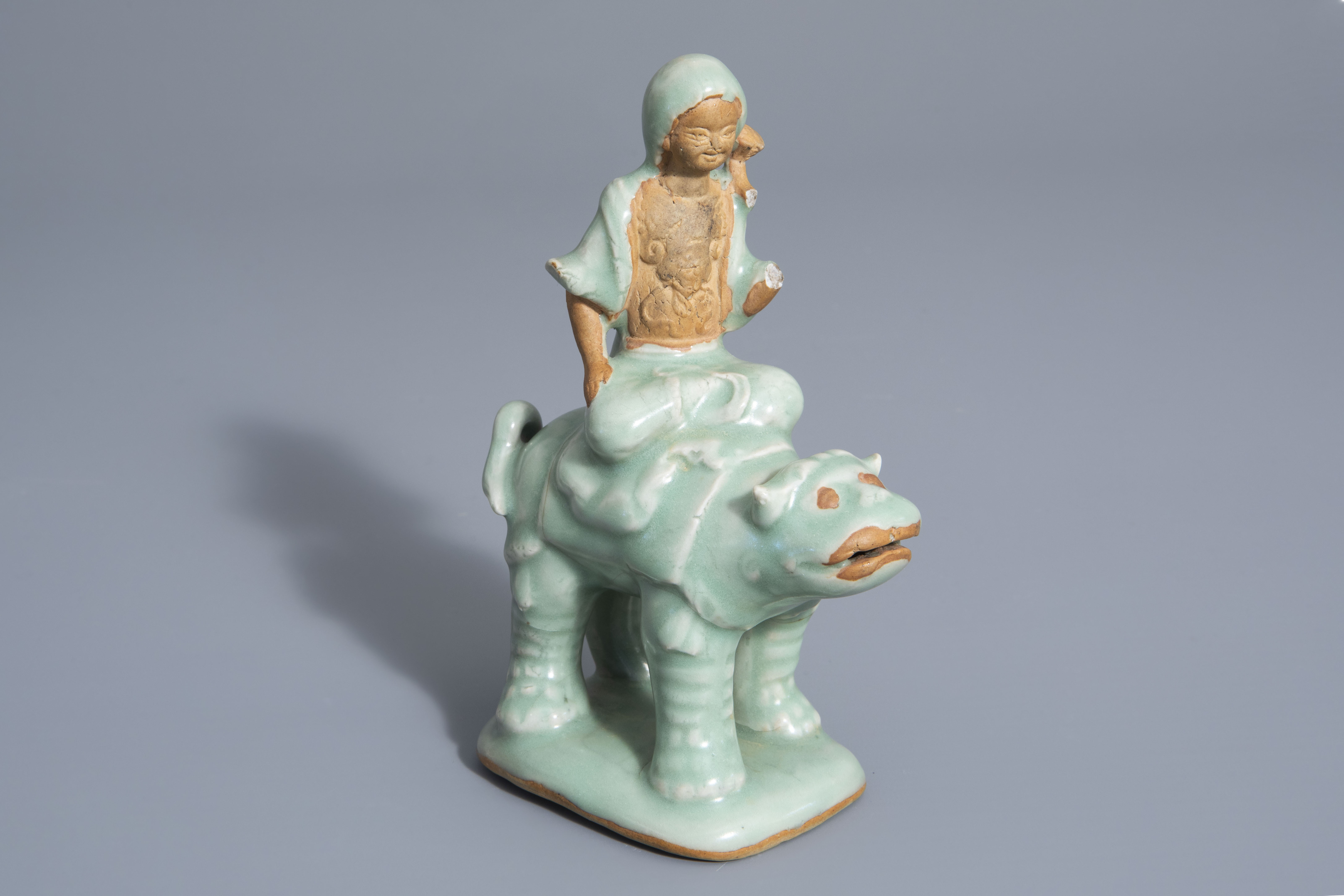 A Chinese celadon glazed group, 19th/20th C.
