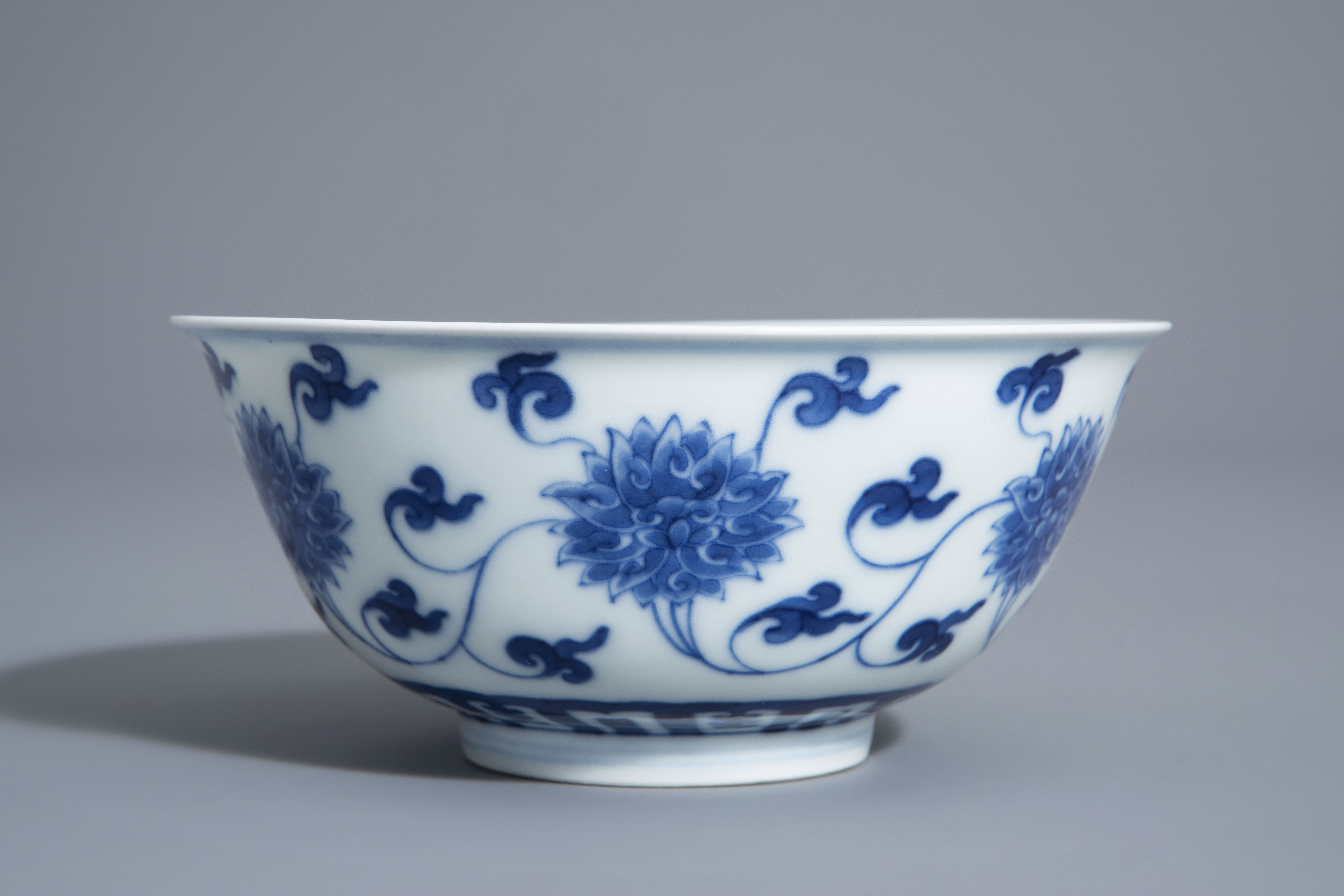 A Chinese blue and white 'lotus scroll' bowl, Kangxi mark, 19th/20th C. - Image 2 of 8
