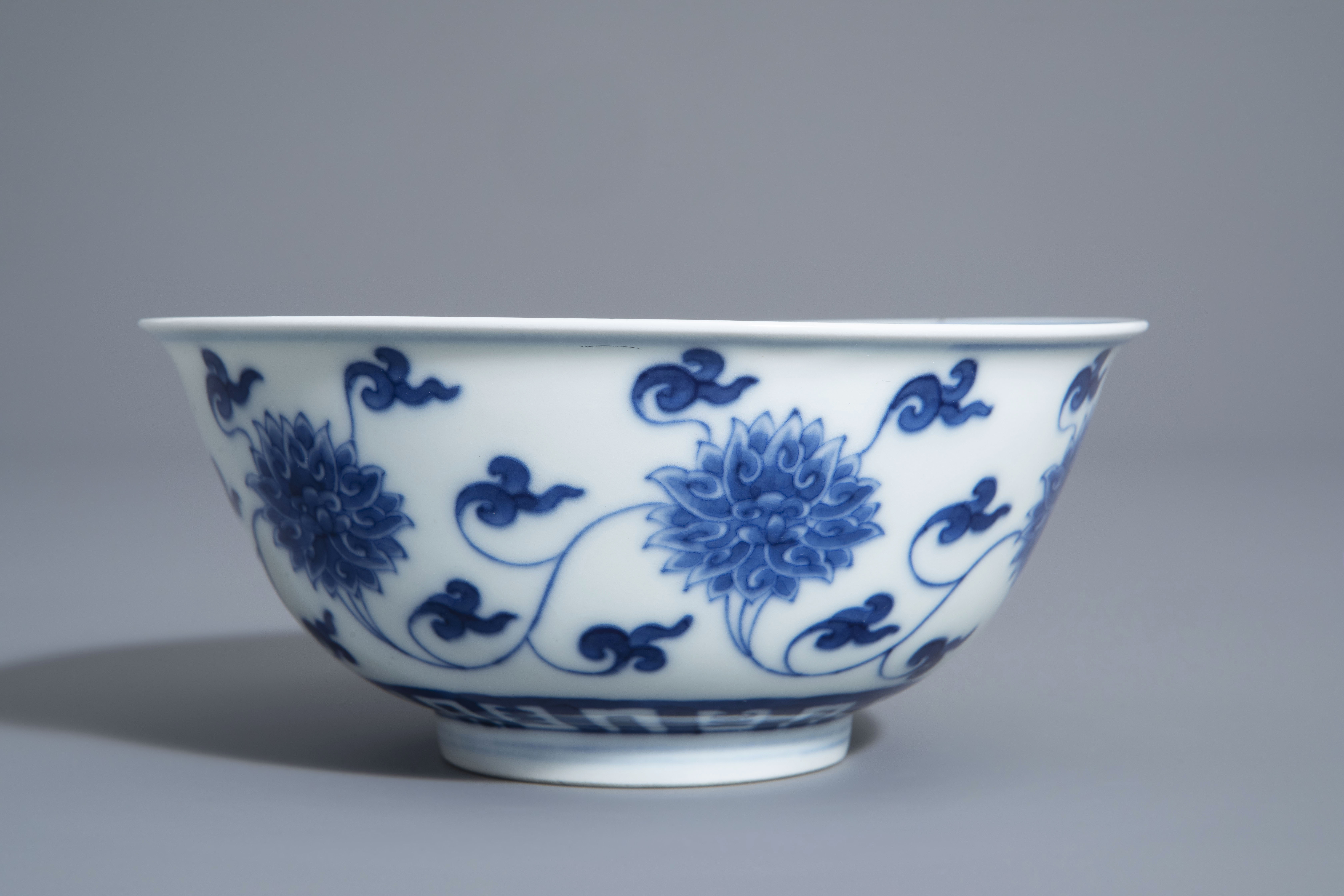 A Chinese blue and white 'lotus scroll' bowl, Kangxi mark, 19th/20th C. - Image 4 of 8