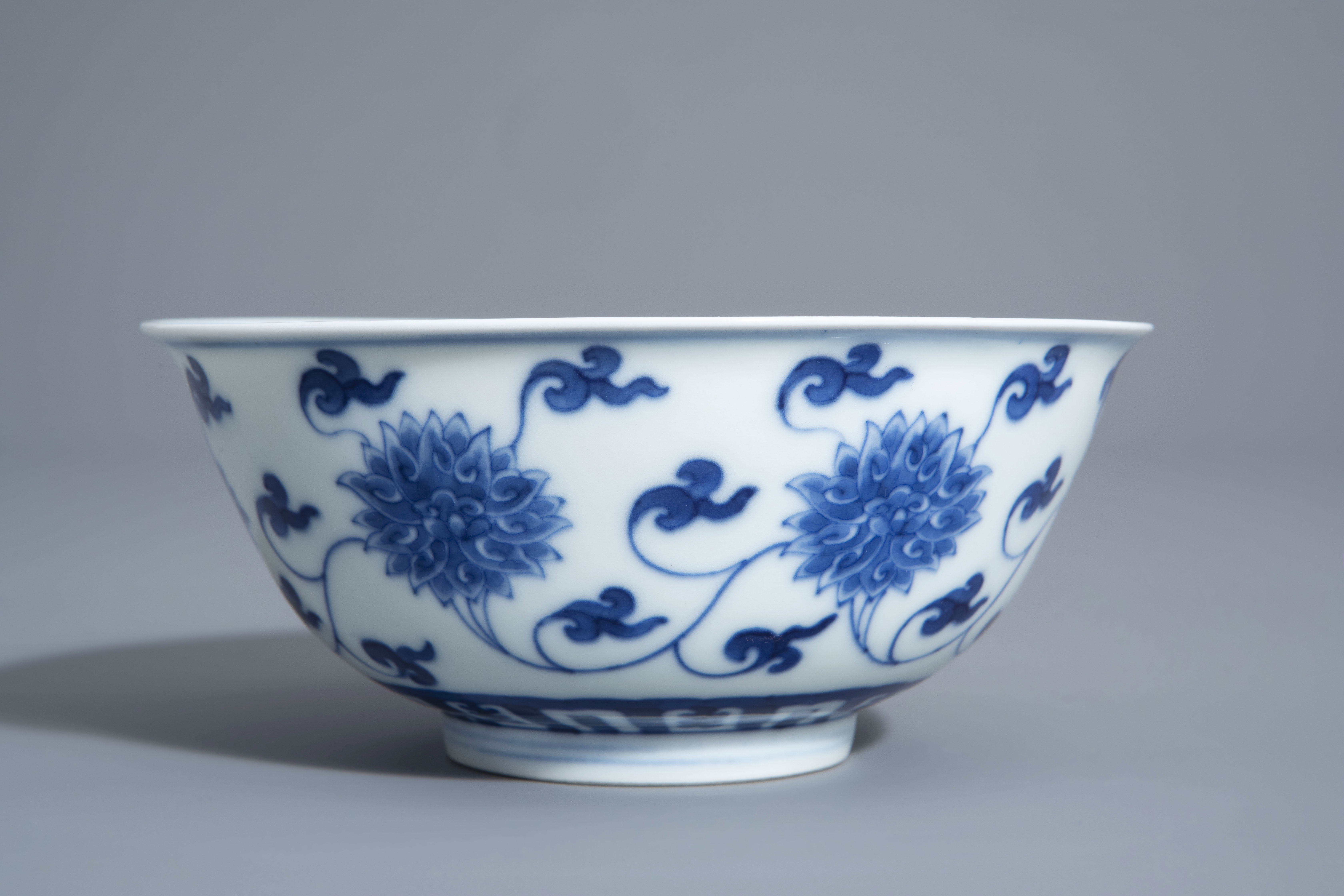 A Chinese blue and white 'lotus scroll' bowl, Kangxi mark, 19th/20th C. - Image 3 of 8