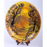 """A Poole Aegean pottery oval charger, decorated with Corfe Castle at sunrise, 15 1/2"""" wide"""