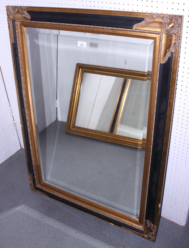 "Lot 442 - An ebonised and gilt framed wall mirror, in deep swept frame, plate 23"" x 35"""