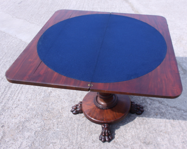 Lot 393 - An early Victorian mahogany fold-over top card table, on turned column and quadruple lion paw