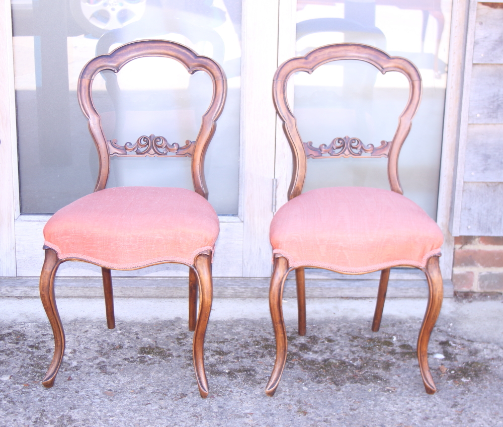 Lot 435 - A pair of Victorian carved walnut loop back side chairs with stuffed over seats, on cabriole