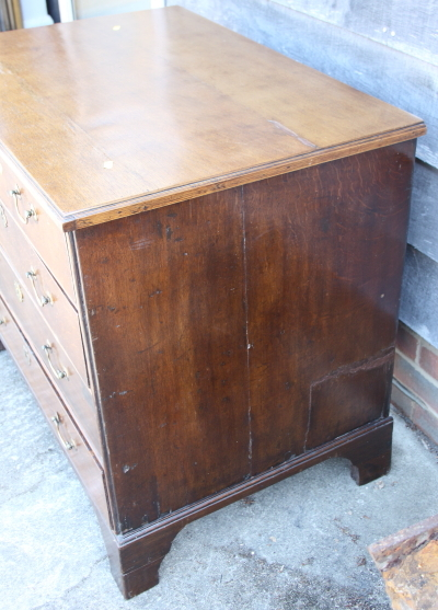 Lot 397 - A late Georgian oak chest of four graduated long drawers with brass bail handles, on bracket feet,