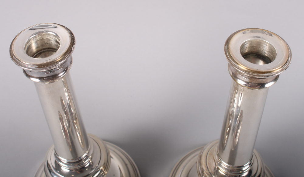 """Lot 218 - A pair of silver cylindrical candlesticks with filled bases, 9 1/2"""" high"""