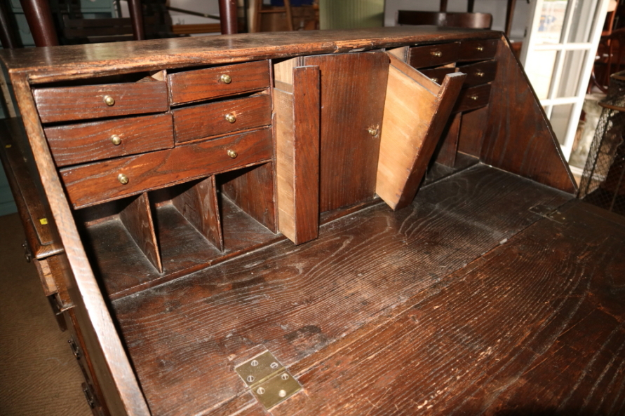 Lot 421 - A late 19th century oak fall front bureau with fitted interior over four long graduated drawers,