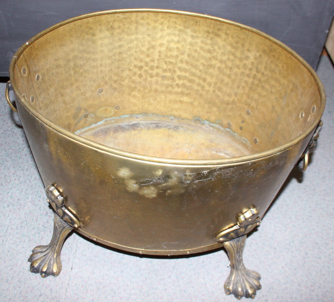 """Lot 91 - A brass oval two-handle log bin with lion paw feet, 17"""" wide"""