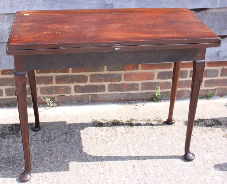 """Lot 410 - A 19th century mahogany fold-over top tea table, on pole turned supports and pad feet, 35"""" wide"""