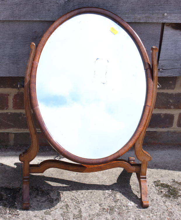 """Lot 443 - An oval swing frame toilet mirror, on skeleton stand, 19 1/2"""" wide"""