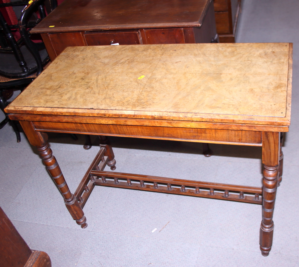 Lot 398 - A Victorian walnut fold-over card table with turned and tapered supports, on galleried 'H'