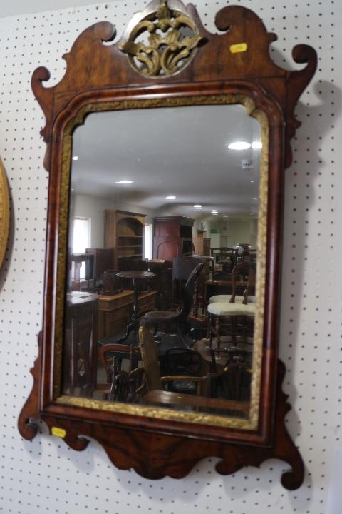 "Lot 441 - A figured walnut framed wall mirror of early Georgian design with pierced gilt crest, plate 19"" x 12"