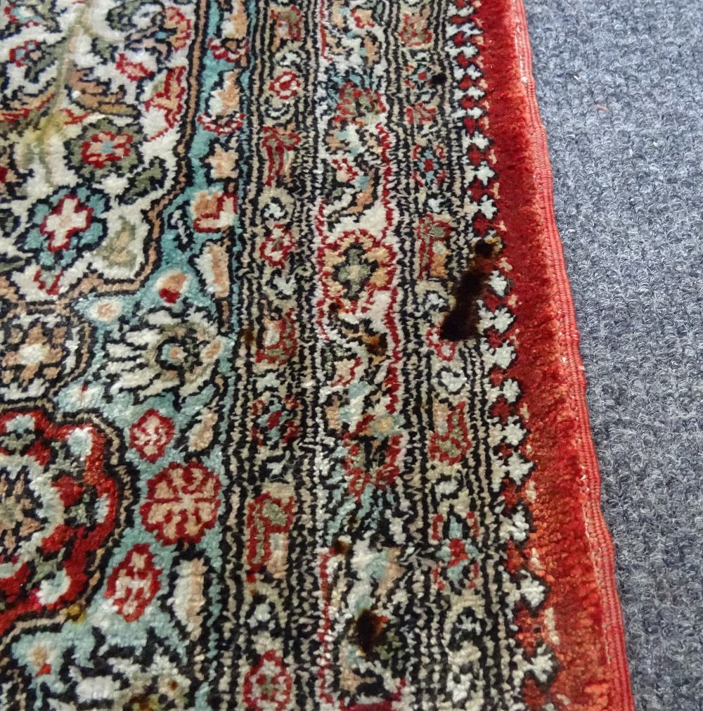Lot 1541 - A silk Hereke rug, Turkish, the madder field with pale medallion and spandrels,