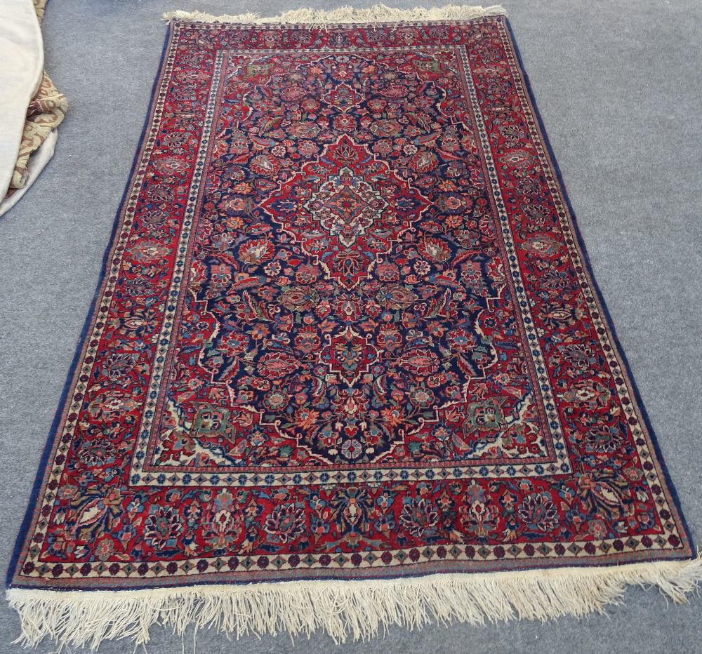 A Kashan rug, Persian, the indigo field with a madder medallion, matching spandrels,