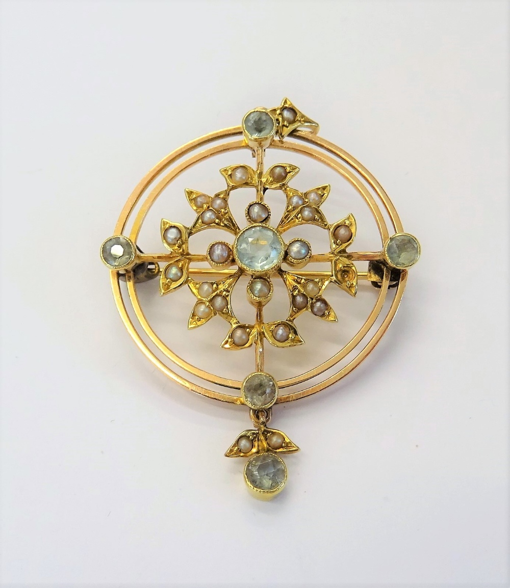 A gold, aquamarine and seed pearl set pendant brooch, in a circular openwork design,