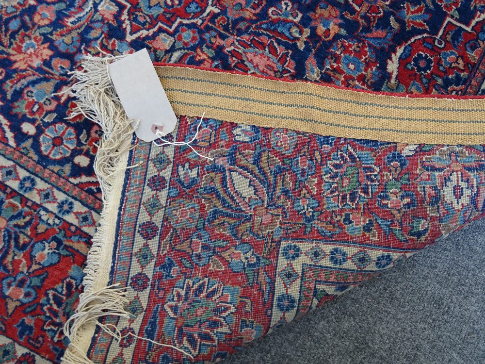 A Kashan rug, Persian, the indigo field with a madder medallion, matching spandrels, - Image 2 of 3