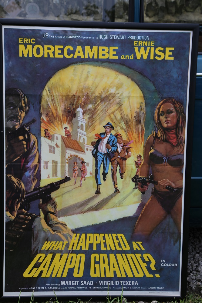 """Lot 16 - Eric & Ernie: Framed Original 1970's cinema poster """"What Happened at Capo Grande?"""" (42 x 29 inches)"""