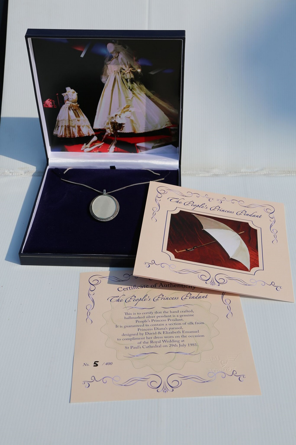 Lot 17 - Princess Diana: Silver Pendant containing a selection of silk taken from her parasol used on her