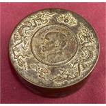 A circular bronze scroll weight with dragon detail to top rim.