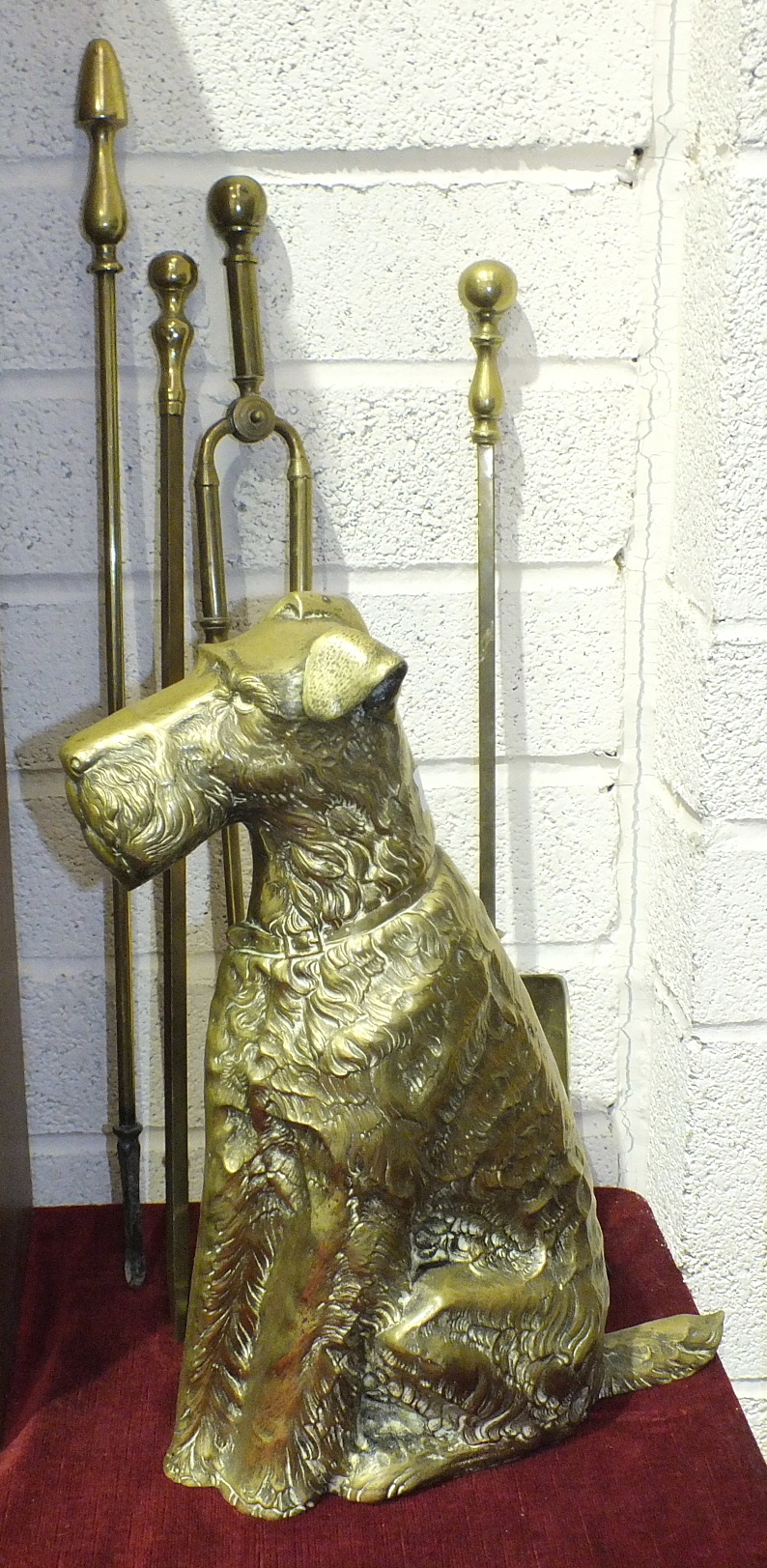 Lot 127 - A brass companion set holder in the form of an Airedale Terrier, 42cm high and three fire