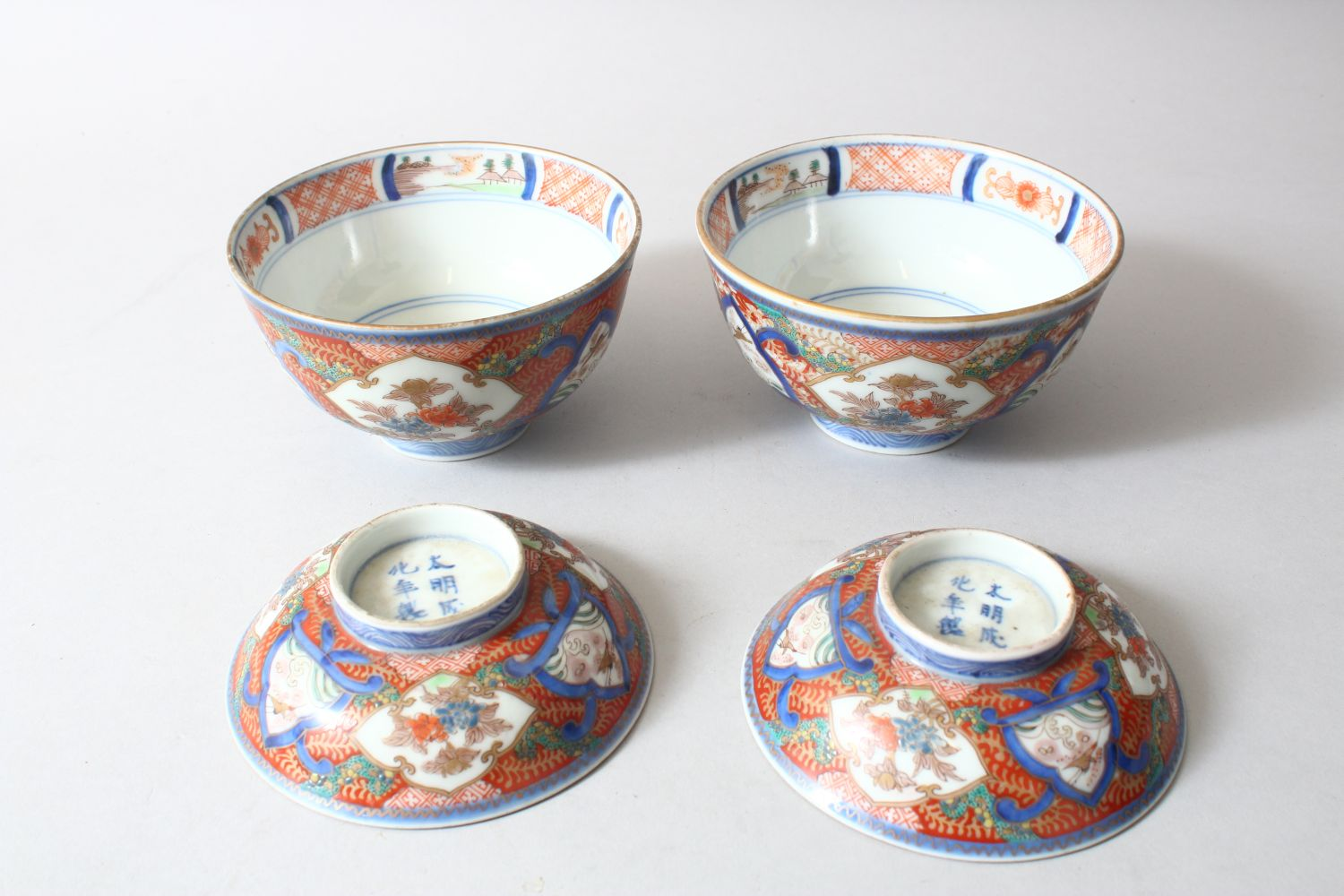 A PAIR OF JAPANESE MEIJI PERIOD IMARI PORCELAIN BOWLS AND COVERS, painted with alternating panels of