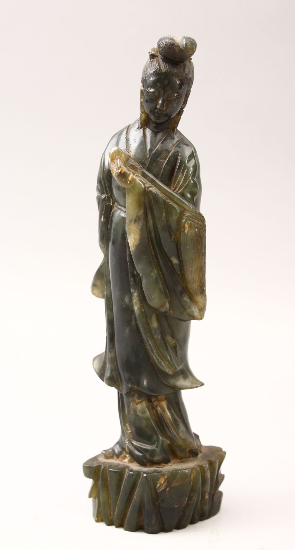 A 20TH CENTURY CHINESE CARVED JADE FIGURE OF GUANYIN, stood upon a stylized stump base holding a