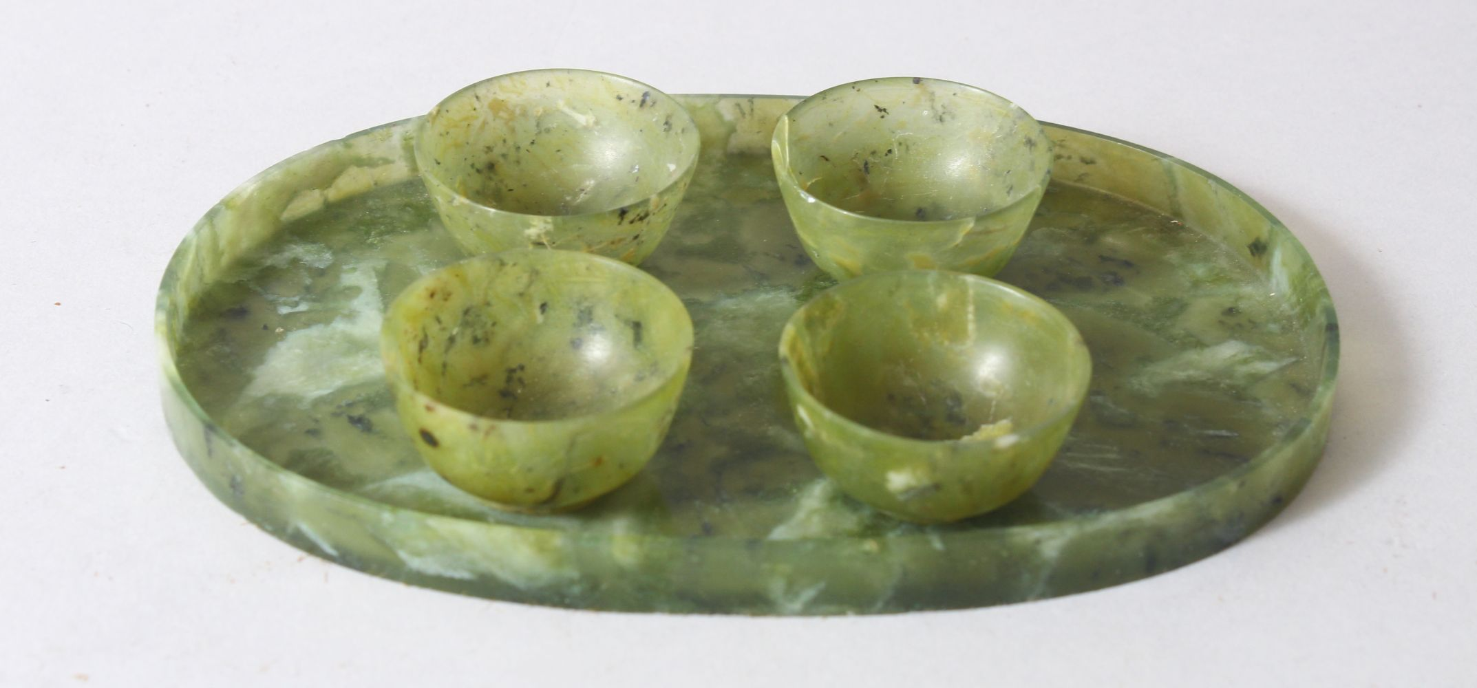 A CHINESE MOTTLED GREEN JADE OVAL TRAY AND FOUR TEA BOWLS, tray 16cm wide.