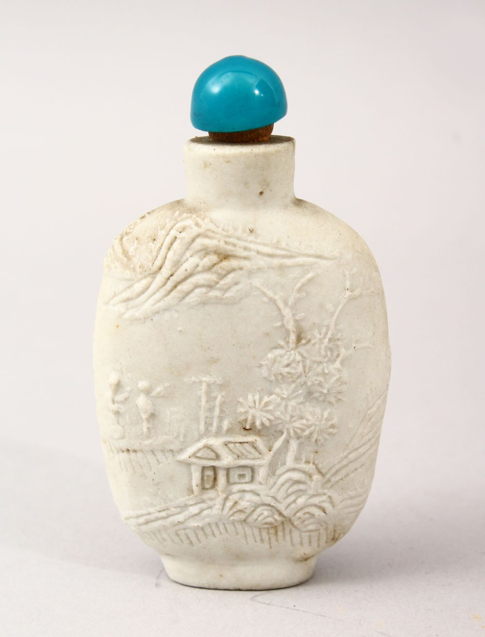 A GOOD 19TH CENTURY CHINESE MONOCHROME PORCELAIN CARVED SNUFF BOTTLE, decorated with scenes of