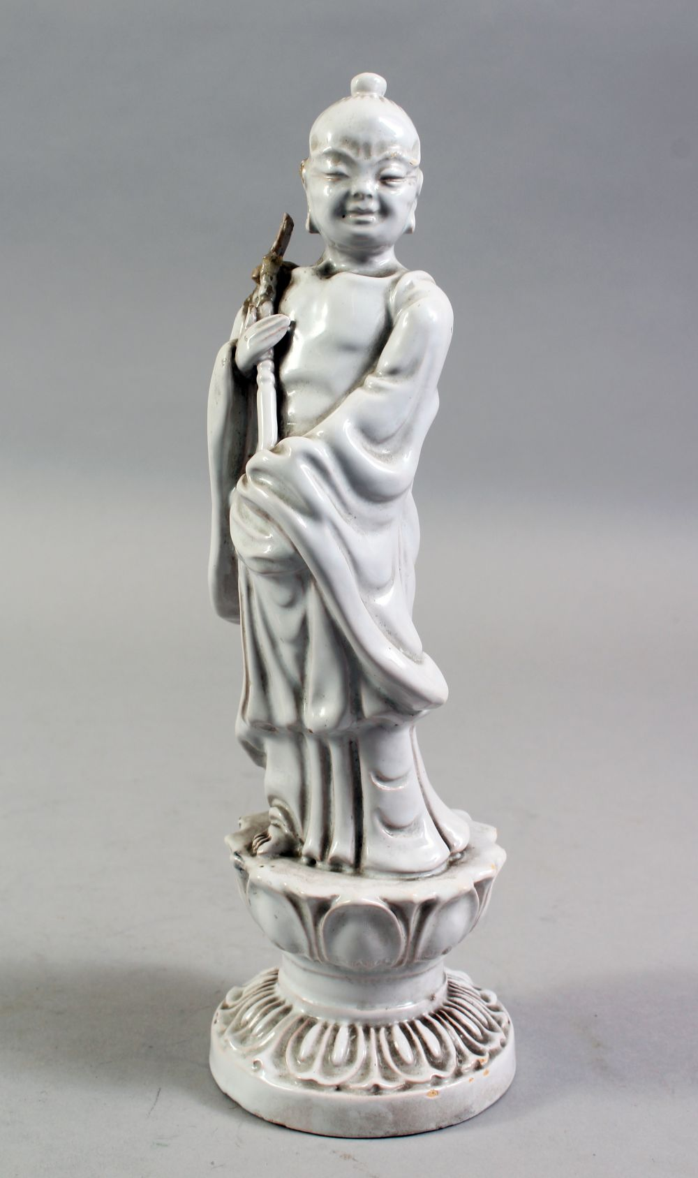 A CHINESE BLANC DE CHINE PORCELAIN FIGURE OF A BOY, standing holding a scepter, on a lotus base,