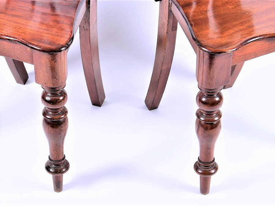 Lot 119 - A pair of mahogany pierced back hall chairs with serpentine-fronted seats on turned front legs, 20th