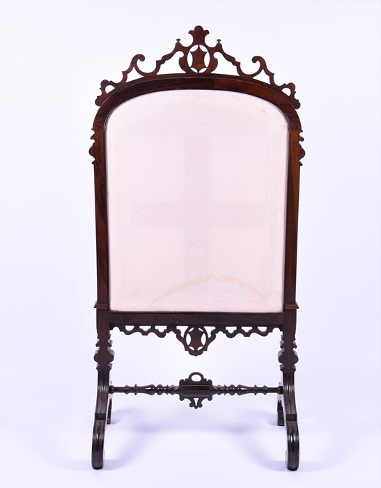 Lot 120 - A large Victorian mahogany carved fire screen  surmounted by shield and scroll decoration, the