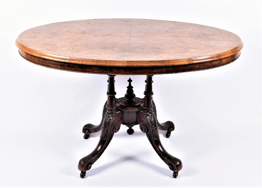 Lot 122 - A late Victorian walnut and inlaid oval loo table with quarter-veneered top, the matched base on