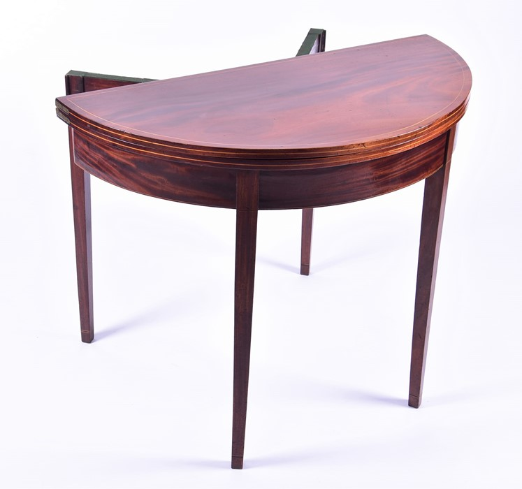 Lot 109 - An Edwardian flame mahogany demi-lune card table with satinwood cross banding and baize lined