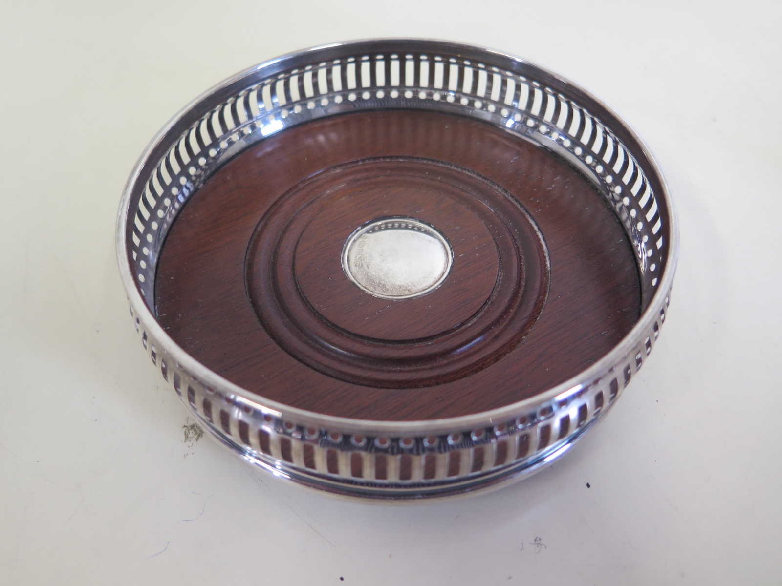 Lot 593 - A pierced silver coaster with wood base and silver button, approx 13cm diameter, in good condition