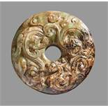 A UNIQUE SWORD POMMEL IN GREEN AND BROWN JADE WITH SCULPTURAL DECORATION OF A DRAGON AND A PHOENIX