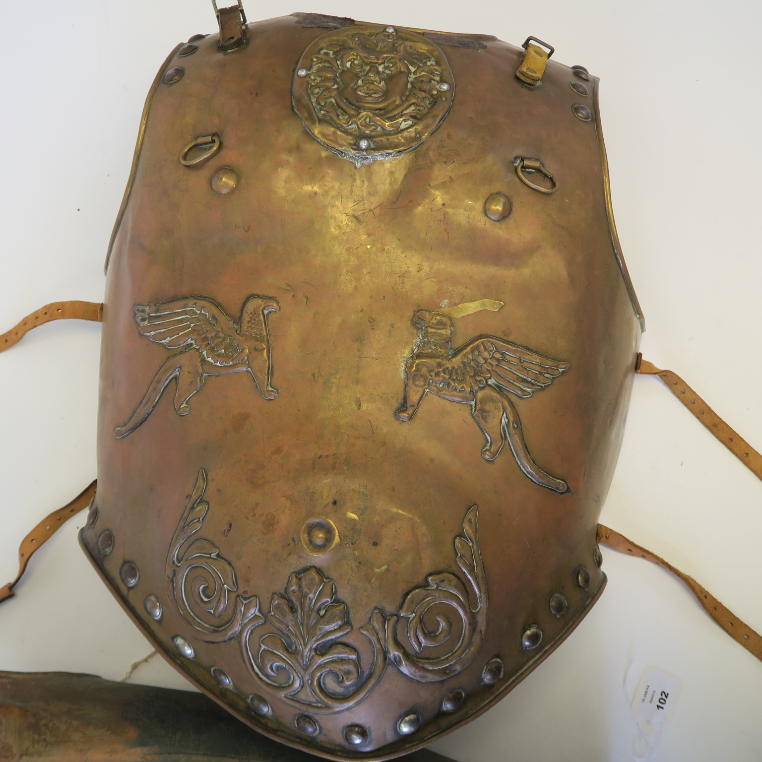 Lot 58 - Metal chest plate movie prop with Medusa head and two griffin's decoration with leather straps and
