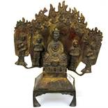 A Tibaten bronze figure flanked by monks with a flamed tankgha style surround, H. 23cm.