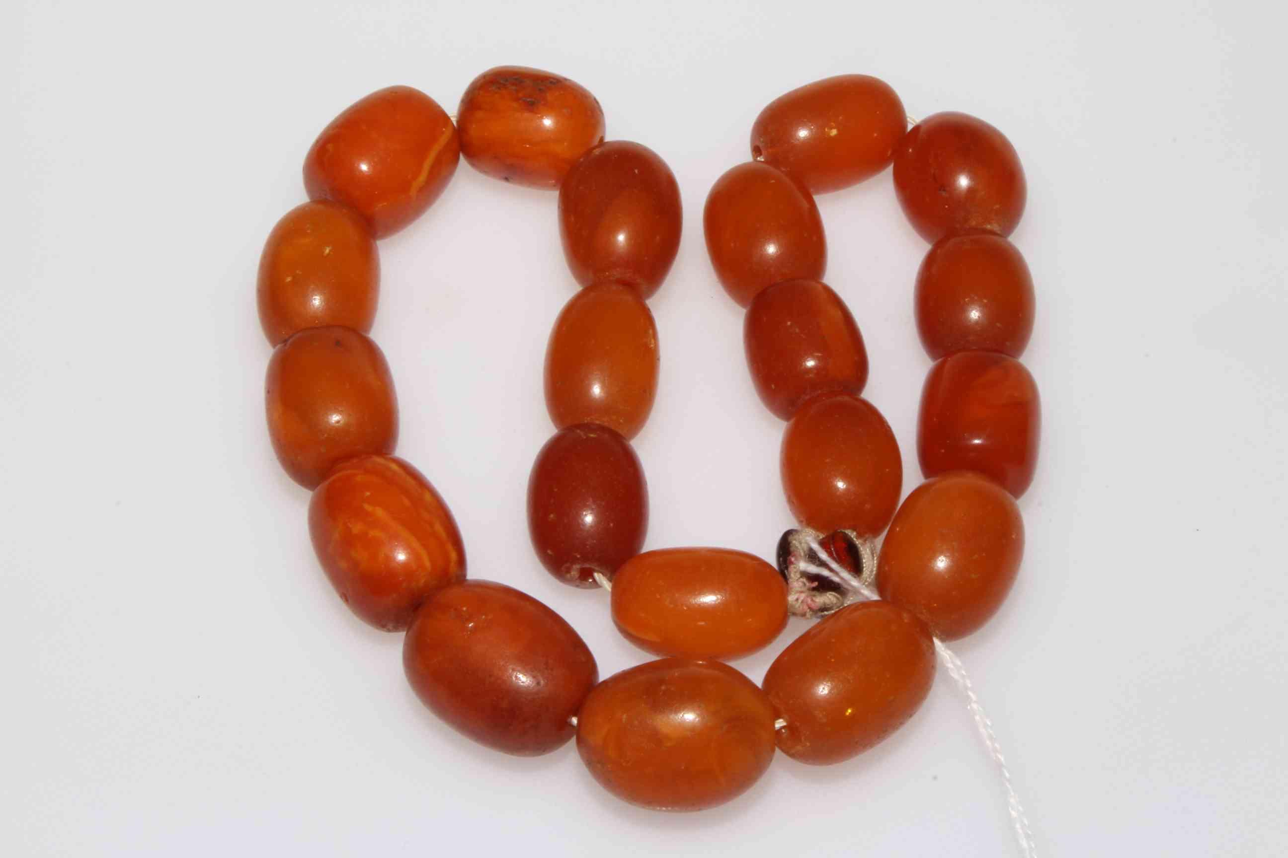 Lot 230 - Necklace of twenty large amber beads, 99 grams.