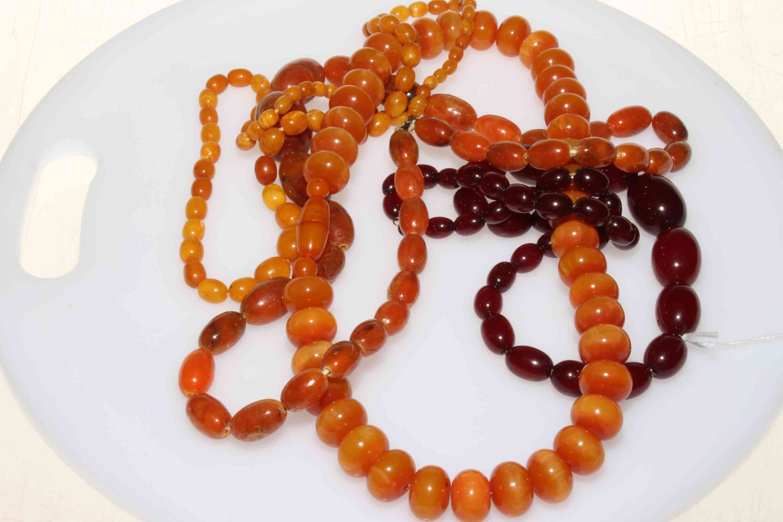 Lot 231 - Necklace of amber beads and three others.