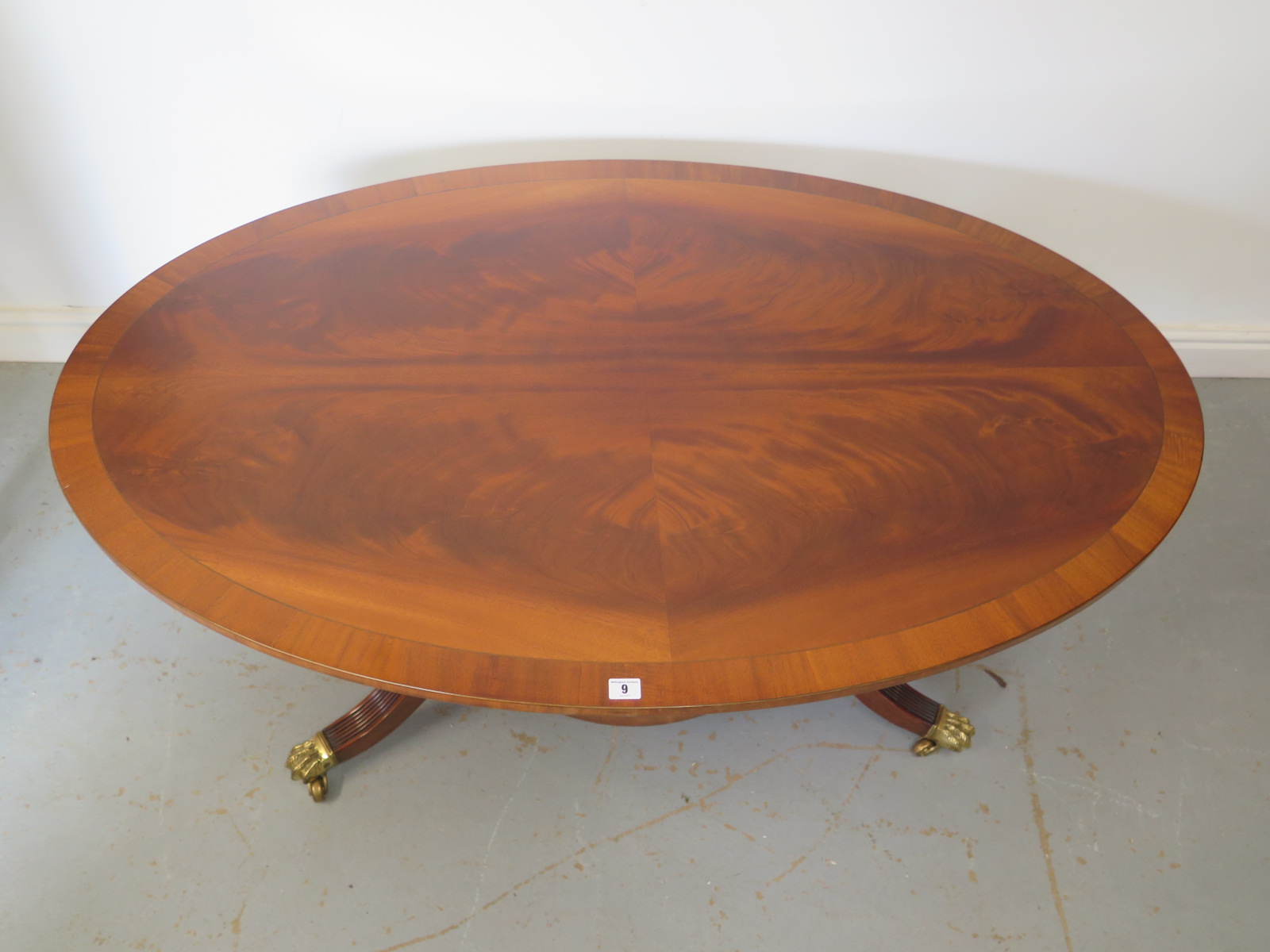 Lot 9 - A modern mahogany veneered oval coffee table on four outswept legs with brass casters - 142cm long x