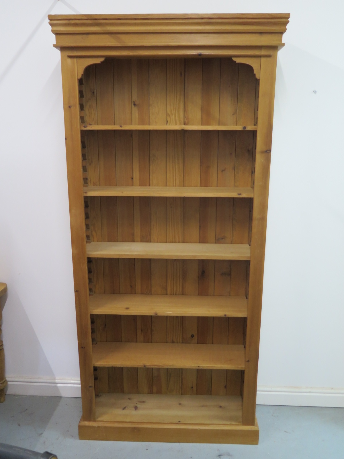 Lot 64 - A modern pine bookcase with adjustable shelving, 210cm tall x 100cm wide x 27cm deep, shelf depth