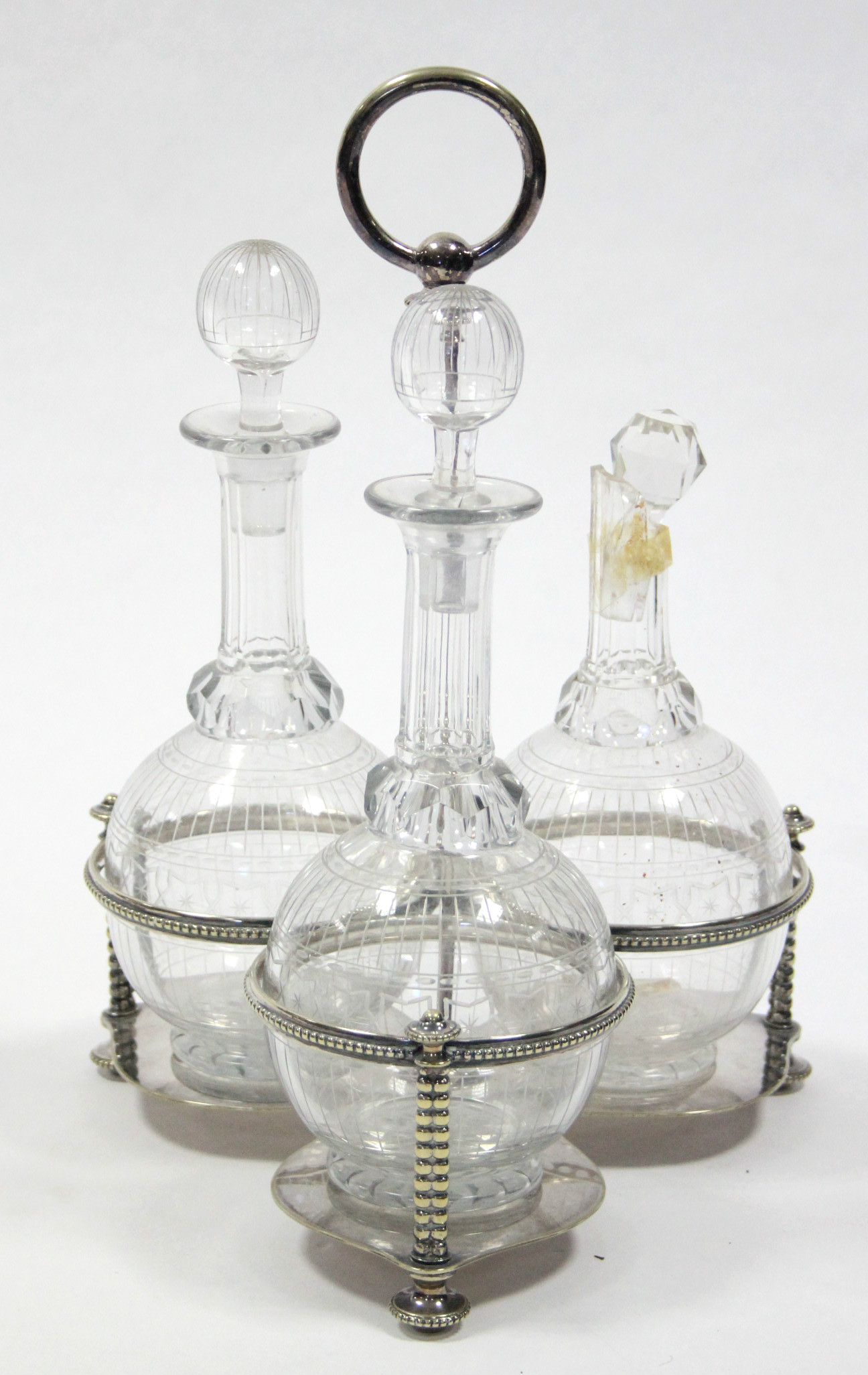 Lot 3 - A late Victorian three-division decanter frame with centre ring handle, fitted three cut-glass