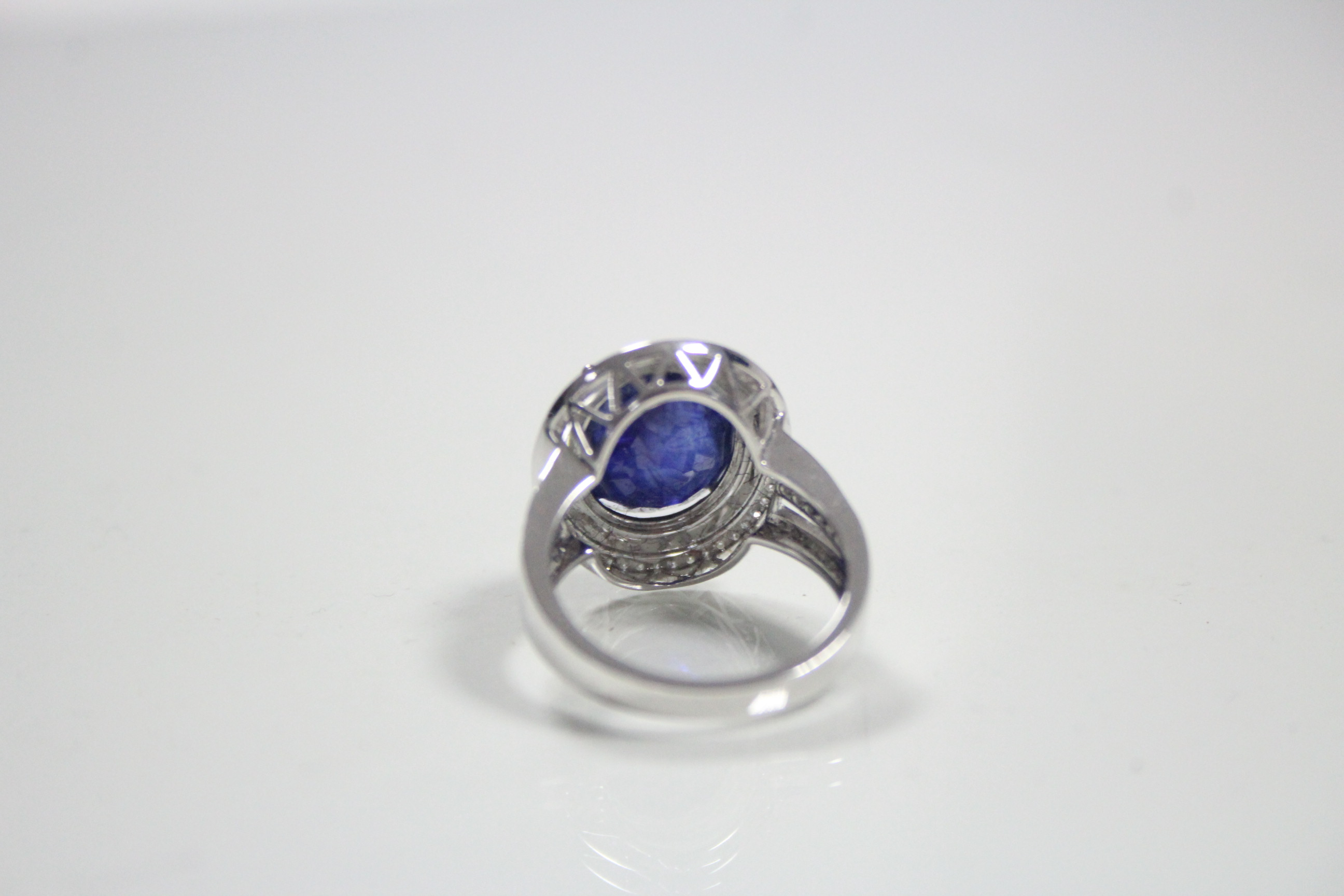 Lot 50 - A white 14K ring set large blue oval-cut gemstone within a double border of small diamonds.