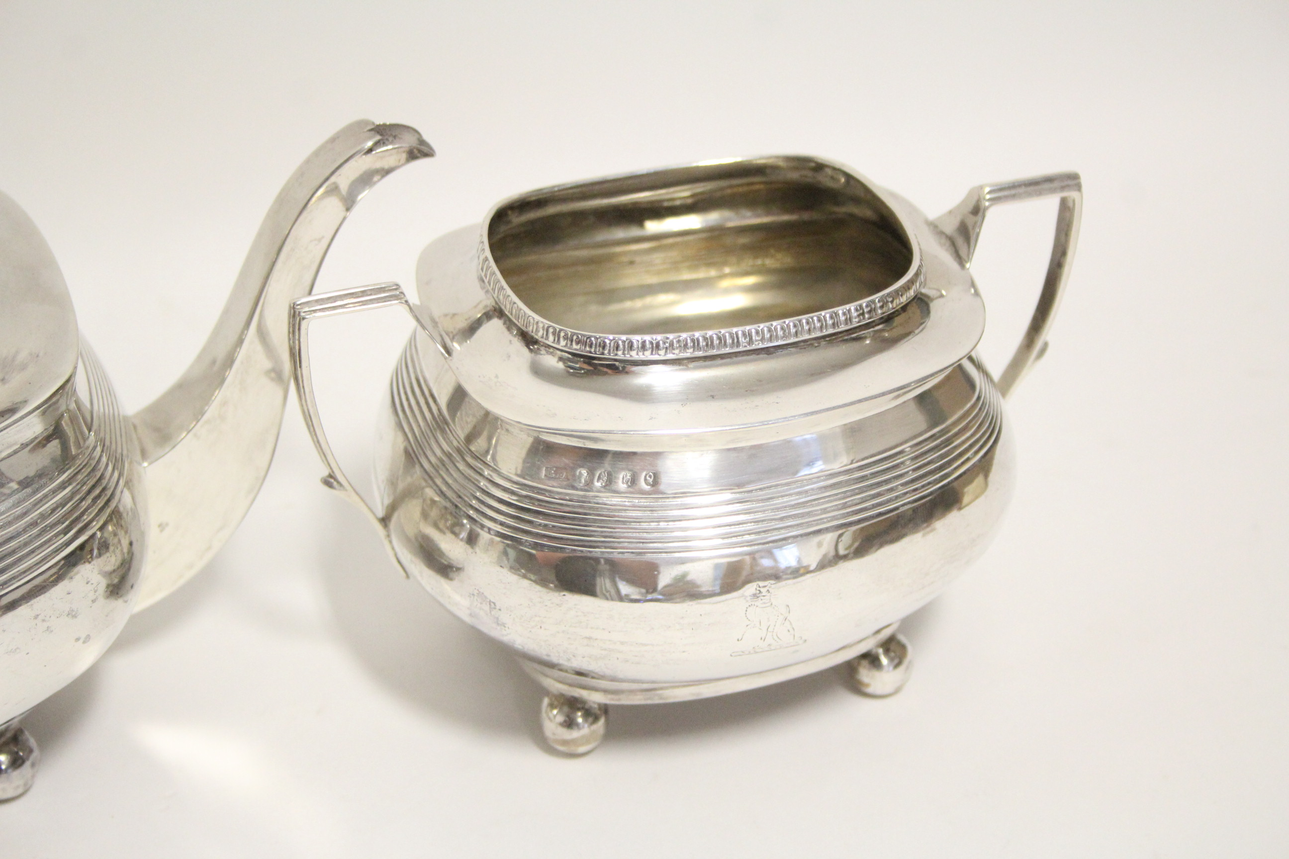 Lot 28 - A George II teapot of compressed oblong form with reeded bands, on four ball feet, London 1810, by