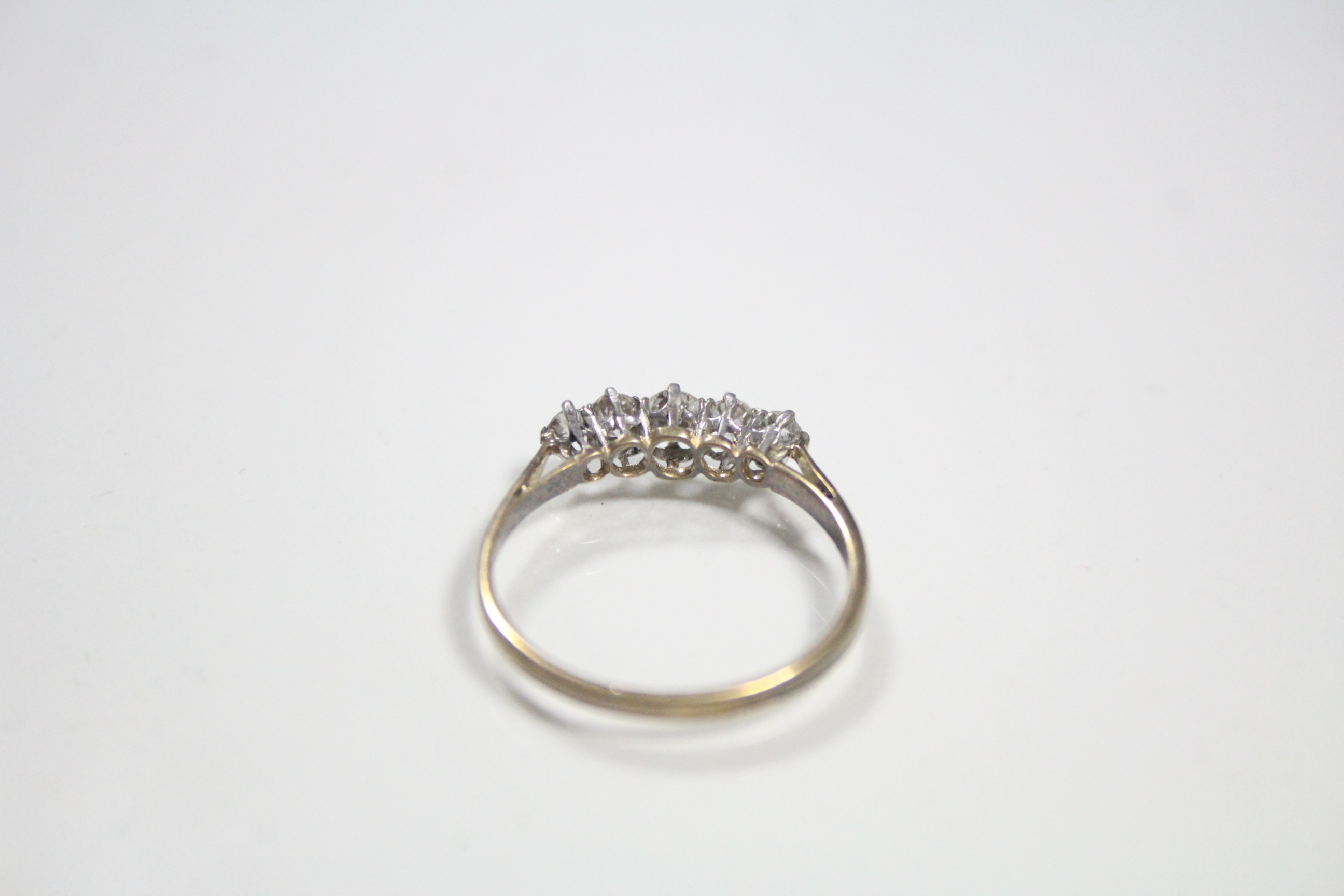 Lot 54 - A diamond ring, the five graduated stones set to an un-marked white metal shank.